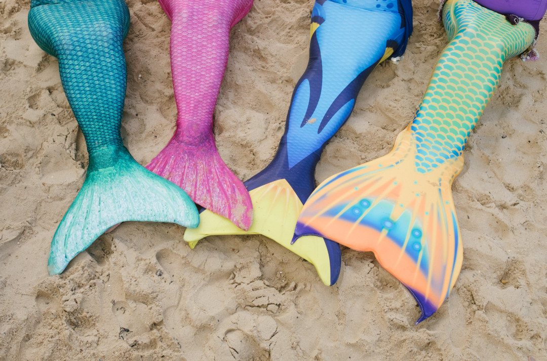 four mermaids' tails together on the sand